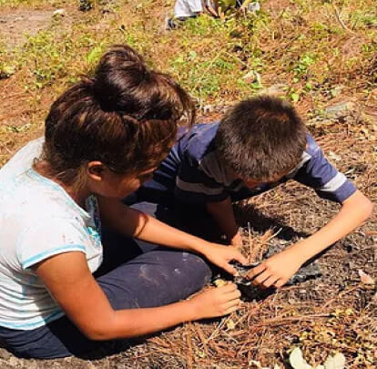 Two students planting in a community garden