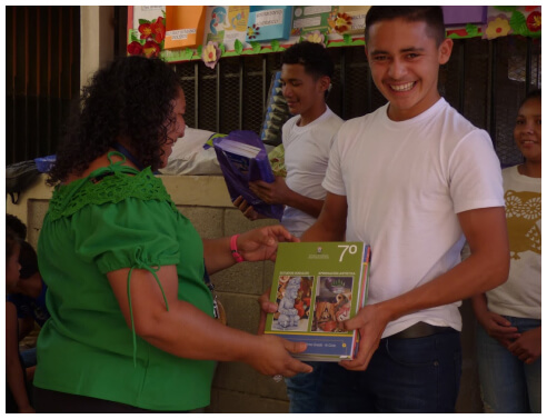 A smiling male teenager is being handed a textbook by a woman in a green blouse in a classroom.