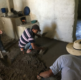 Two men contructing a cement floor for a school